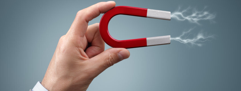 a hand holding a magnet demonstrating a magneting field which is used for adhesive debonding