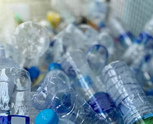 pile of pet bottles with labels glued using alkali soluble labeling adhesive