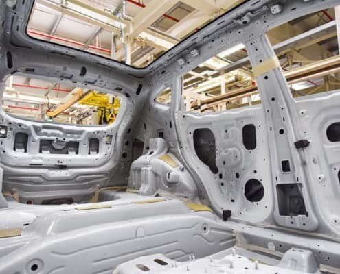 hot melt body panel adhesive being applied to vehicle frame